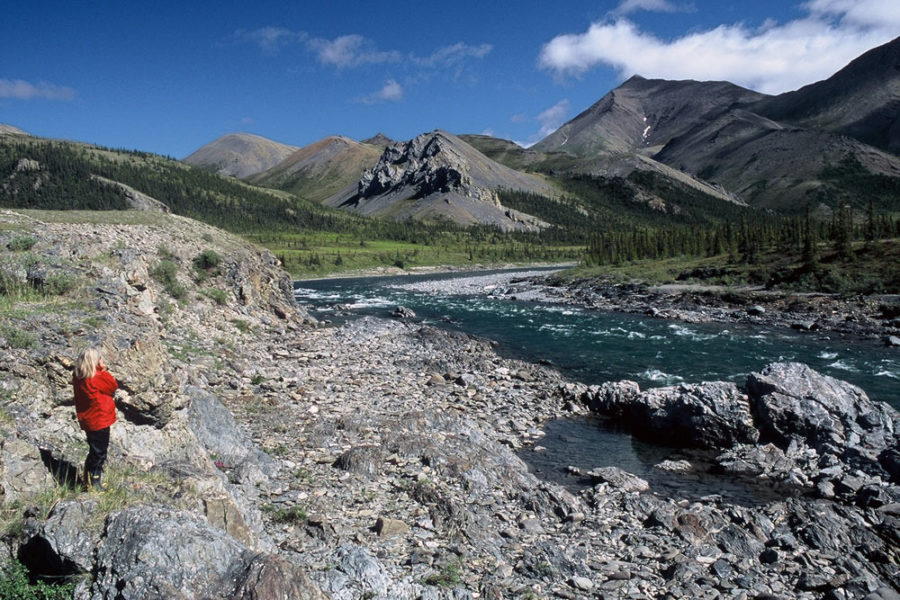 Hiker next to river, Firth River Rafting, Ivvavik National Park, Yukon Territory.