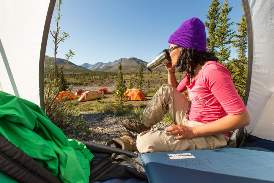 Rafter enjoying morning coffee in tent, Firth River Rafting, Ivvavik National Park, Yukon Territory.