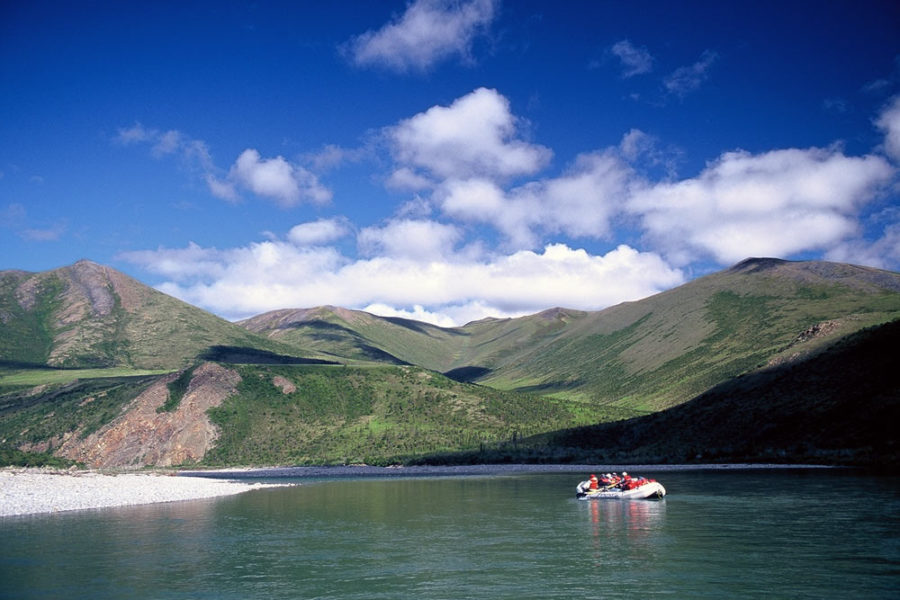 Raft on river with mountains in backdrop, Firth River Rafting, Ivvavik National Park, Yukon Territory.