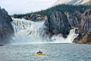 Rafters in front of Virginia Falls on the Nahanni River in Nahanni National Park and UNESCO World Heritage Site.