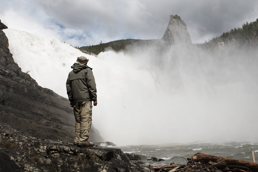 Standing below the thundering Virginia Falls on the Nahanni River in Nahanni National Park Preserve.