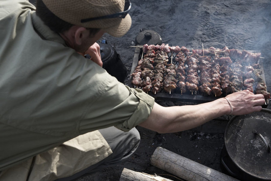 A guide grills some kebabs over an open fire on the shores of the Nahanni River in Nahanni National Park Preserve.