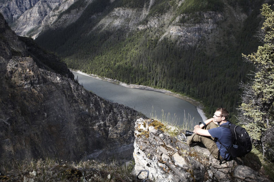 Hiker perched high above the Nahanni River in Nahanni National Park Preserve in Canada's Northwest Territories.
