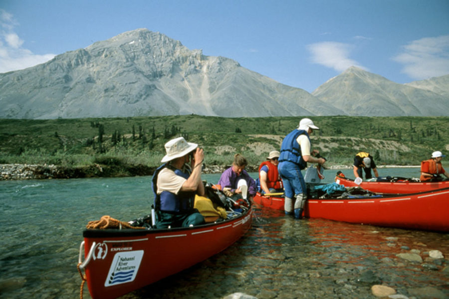 Several canoes on the Snake River in Yukon, Canada with mountains in the background.