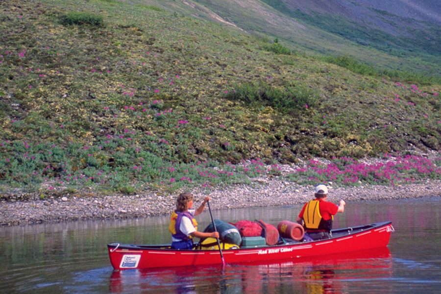 A couple paddling a canoe on the Snake River in Yukon, Canada through the Peel Watershed.