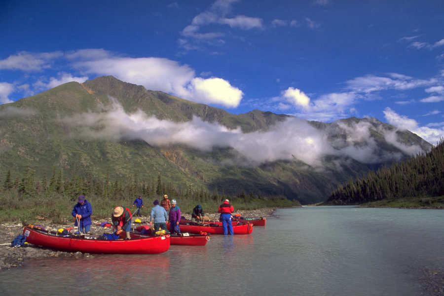 Several canoes on the shore of the Snake River in Yukon, Canada with mountains in the background.