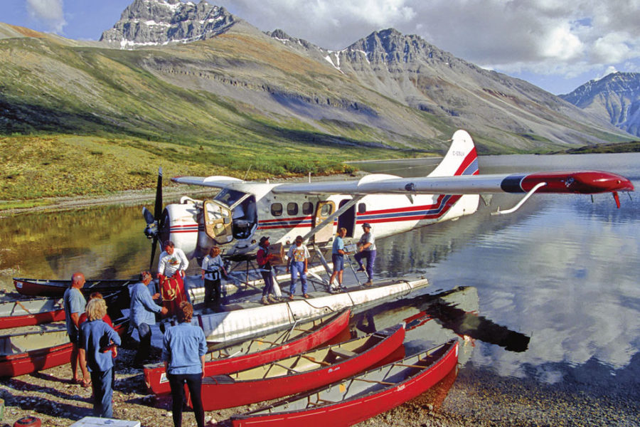 Float plane on lake with paddlers unloading canoes and gear in preparation for paddling the Snake River in Yukon, Canada.