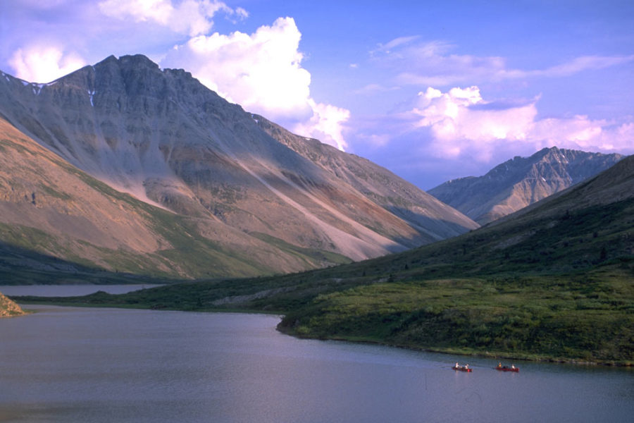 Two Canoes on the Snake River in Yukon, Canada. They appear dwarfed by massive mountains in the background.