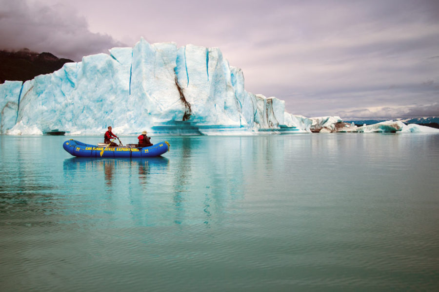 Rafters floating next to iceberg on our Alsek River Rafting Expedition.