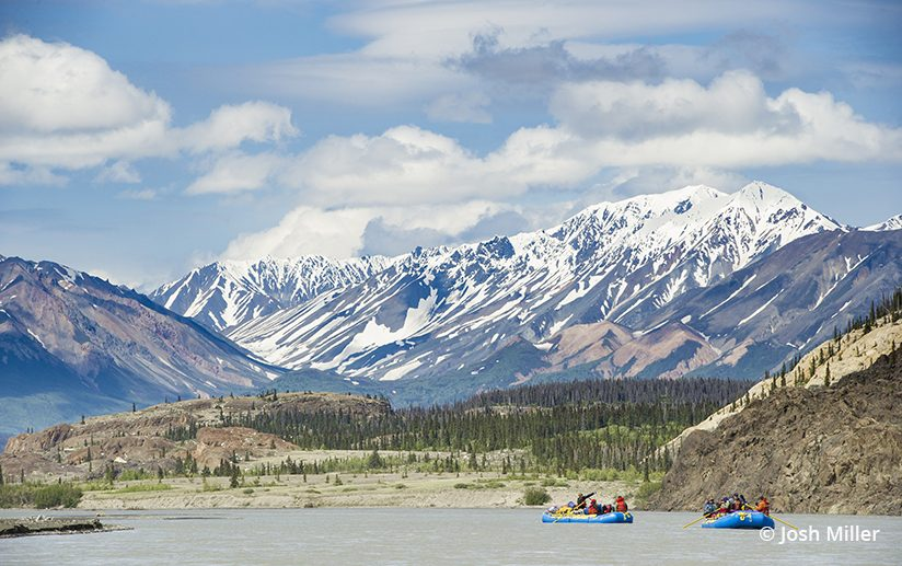 Rafts line up for a moment beneath towering peaks on the Alsek River.