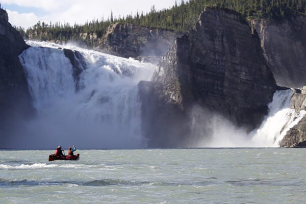 Couple paddling canoe next to Virginia Falls on the Nahanni River