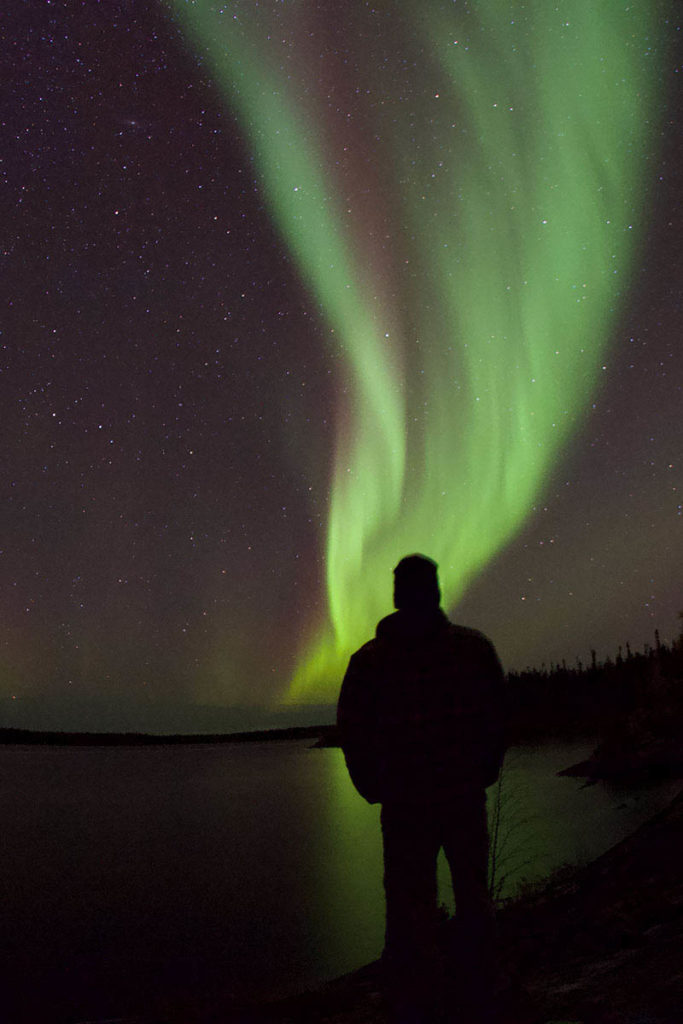 Man standing next to lake, watching the northern lights dance in the sky above.