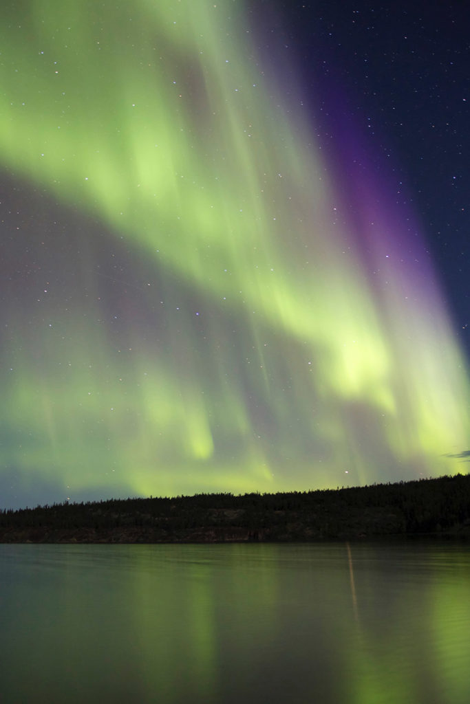 Northern Lights fill the sky above a lake in the Northwest Territories, Canada.