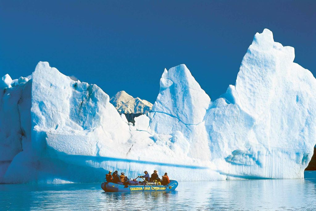 Rafters floating next to an iceberg on Alsek Lake on a journey down the Tatshenshini River.