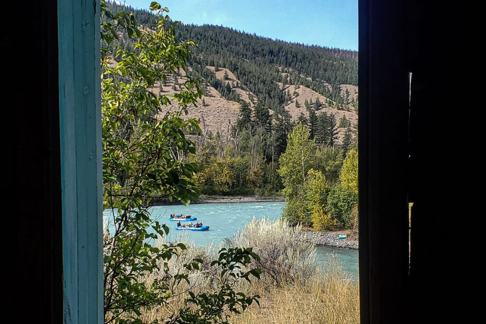 Photo: Looking through a window frame at two rafts descending a set of rapids.